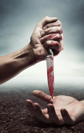 Bloody human hand with knife under another hand