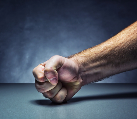 thumbs: Male fist on the table in dark room