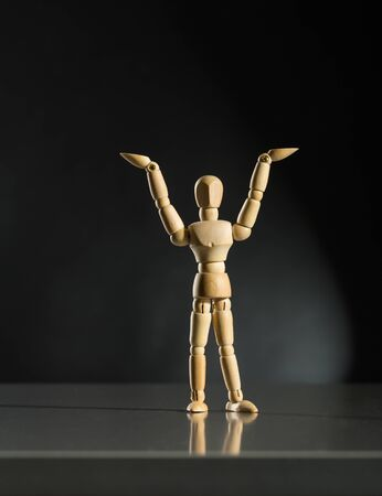 artists dummy: Human wood manikin raising hands up against dark background Stock Photo