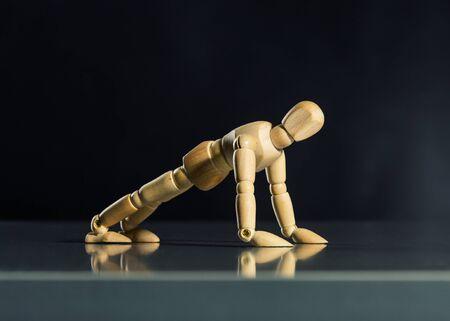 artists dummy: Human wood manikin doing push-ups against dark background