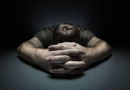 Trieste man op de tafel in een donkere kamer