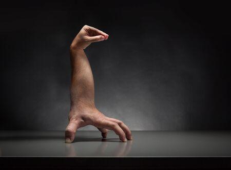 figuras abstractas: criatura extraña mano humana sobre la mesa gris