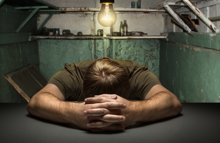 abandoned room: Sad man on the table in the old abandoned room Stock Photo