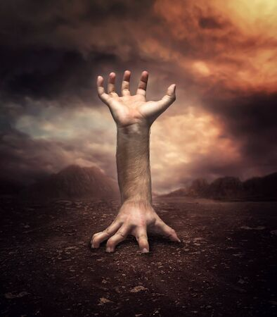 Strange human hand in the desert at night