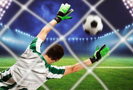 arquero de futbol: Vista posterior del portero agarrar la pelota en el campo de fútbol