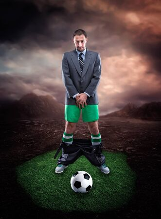 genitals: Businessman in sportwear protecting his genitals looks at the football