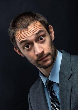 viso uomo: Sorpreso uomo d'affari con la barba su sfondo scuro