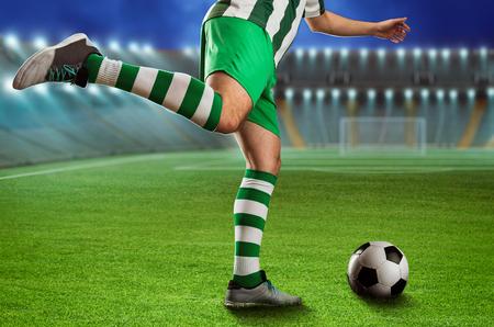 terrain foot: Football-joueur bottant le ballon sur le terrain de football
