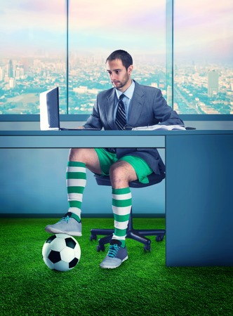 pelota de futbol: Hombre de negocios en pantalones cortos y con una pelota debajo de la mesa