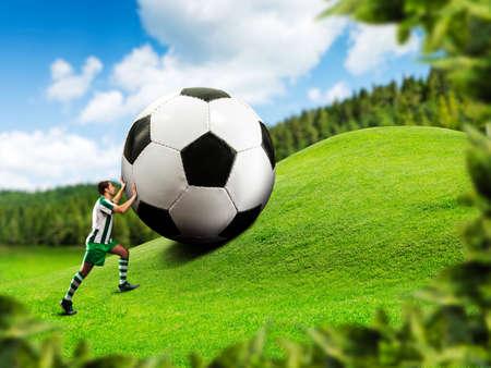 big ball: Football-player pushing a big ball on the hill Stock Photo