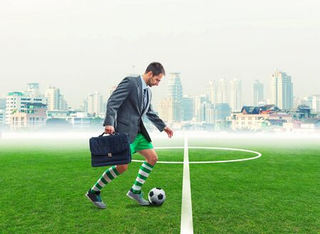 Businessman with suitcase in sportwear playing football in the town stadium