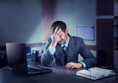 overloaded: Frustrated businessman holding his head sits in the office at night Stock Photo