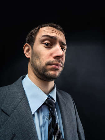 questionable: Portrait of suspicious businessman over dark Stock Photo