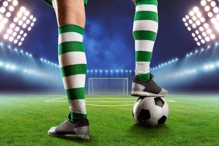 football teams: Football player legs with a ball standing on the football ground