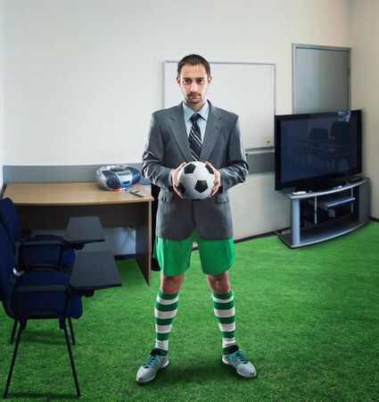 play ground: Businessman in sportwear holds a ball standing in the office