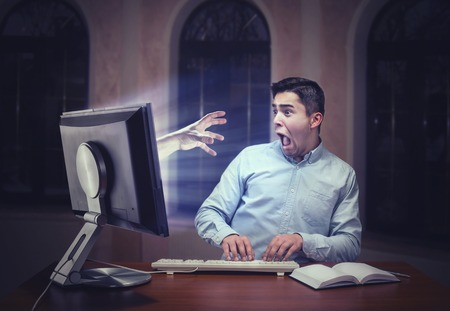 Human hand from the screen scaring a young businessman