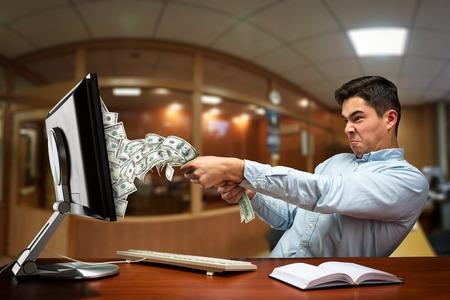 Biznesmen wyciągając pieniądze na ekranie komputera