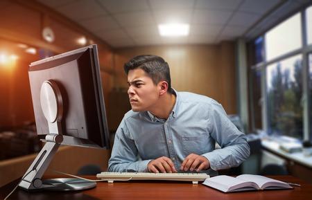 trabajando duro: hombre de negocios joven que trabaja duro en la oficina con el ordenador