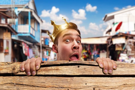 pauper: Scared pauper man with crown on the head hidding behind the wooden bench in slums