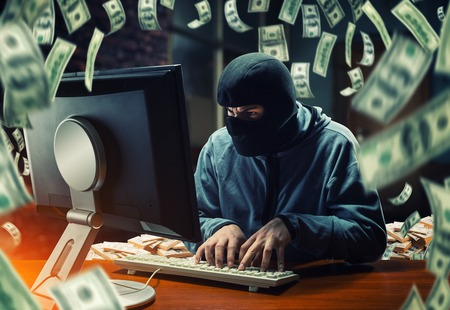 Hacker in mask stealing information and money in the office Stock fotó