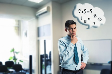 arithmetic: Young businessman doing mental arithmetic in the office