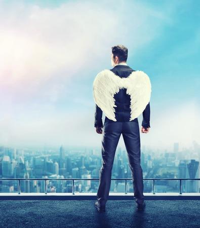 천사 날개를 가진 사업가 건물의 꼭대기에 서있는 그의 뒤쪽에