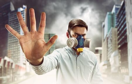 Young man in gas-mask in night town with atmospheric pollution shows stop hand sign