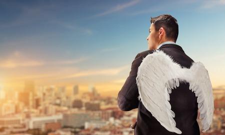 angel de la guarda: Hombre de negocios con alas de ángel en su espalda mirando a la ciudad Foto de archivo