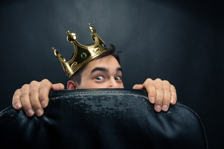 Scared man with crown on the head hidding behind the chair