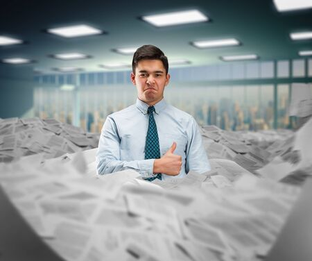 disheartened: Businessman standing in the heap of the papers showing thumb up Stock Photo