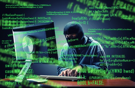 Hacker in mask stealing information in the office 스톡 콘텐츠