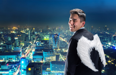 angel: Businessman with angel wings on his back looking at night city Stock Photo