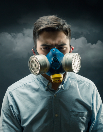 gasmask: Young man in a gas-mask with atmospheric pollution