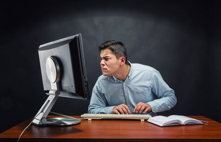 hard day at the office: Young businessman working hard with a computer Stock Photo
