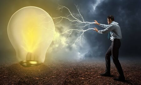 powerful creativity: Businessman with lightnings from his palms turning on the lamp