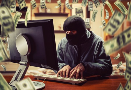 Hacker in mask stealing information and money at home Archivio Fotografico