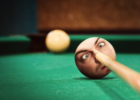 strange: Billiard player aiming to ball with strange male face Stock Photo