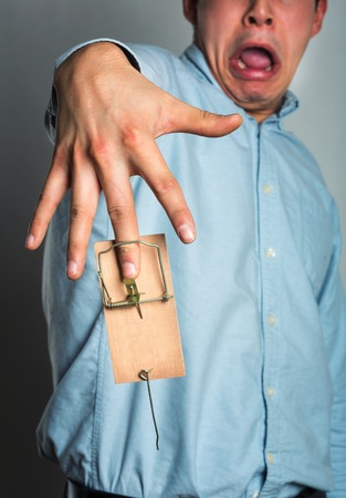 mantrap: Businessmans finger catched in the mousetrap over grey Stock Photo