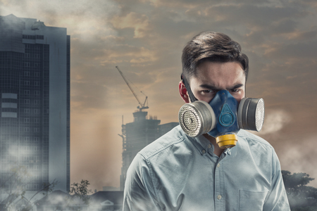 gasmask: Young man in a gas-mask in night town with atmospheric pollution Stock Photo