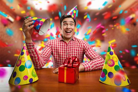 felicitaciones cumpleaÑos: Hombre sonriente joven que juega con el sombrero de cumpleaños en la mesa Foto de archivo