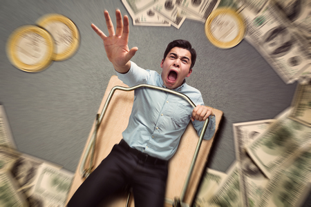 bear trap: Young businessman in a mouse trap with money falling Stock Photo