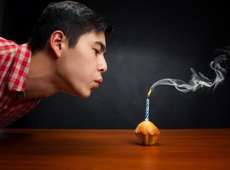 candela: Ragazzo di compleanno che spegne una candela in una piccola torta Archivio Fotografico