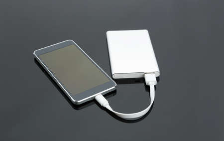 fixed disk: External power bank connected with a smartphone on the table