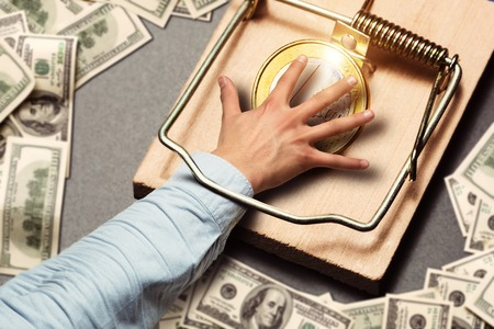 mantrap: Male hand picking a gold coin catched in the mousetrap Stock Photo