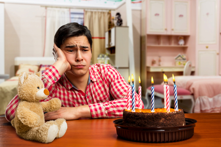 Sad birthday boy and cake with candle at the table Stock Photo - 56352002