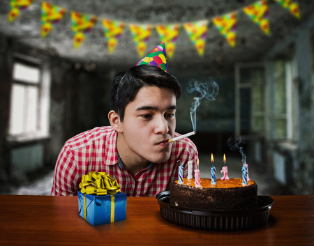 abandoned room: Sad birthday boy smoking in an abandoned room with cake and present