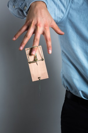 mantrap: Businessmans finger catched in the mousetrap Stock Photo