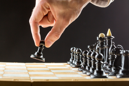 pawn adult: Close up of mans hand playing chess