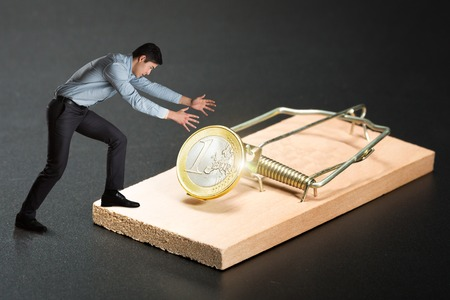 mantrap: Businessman trying to pick a gold coin in the mousetrap Stock Photo