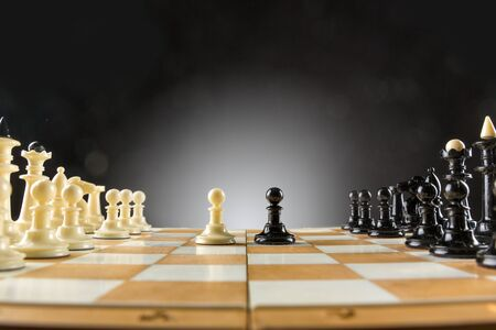 Chess figures on the board started to fight Stock Photo